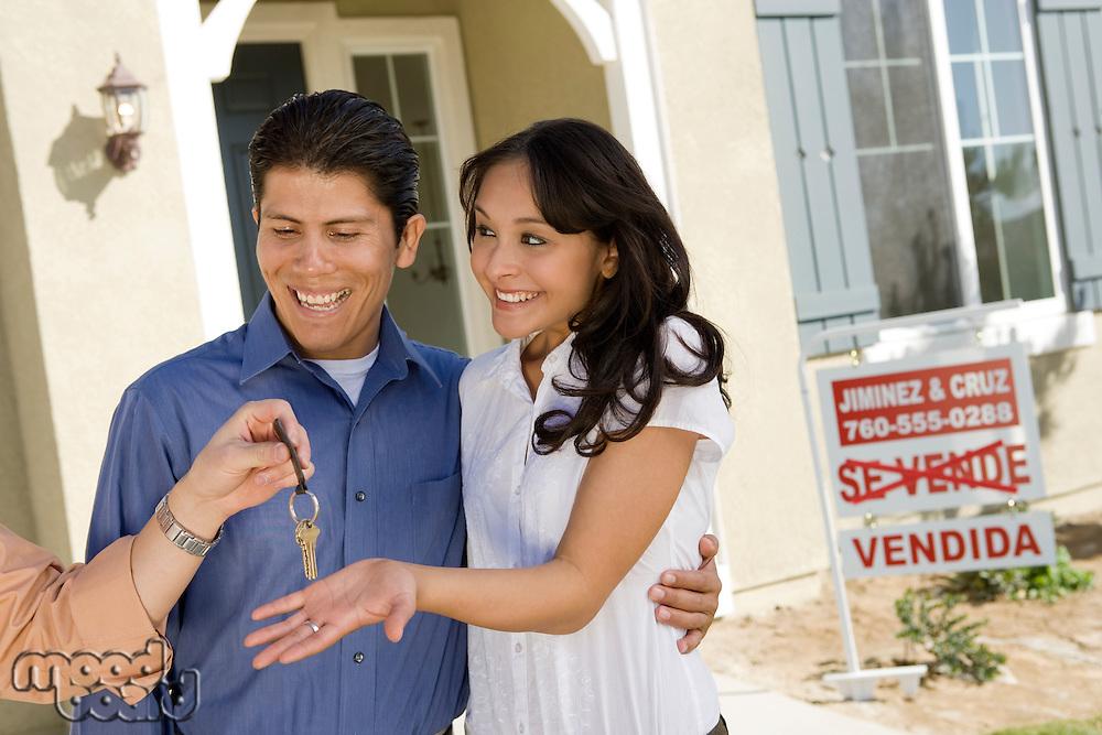 Young couple buying house, taking keys