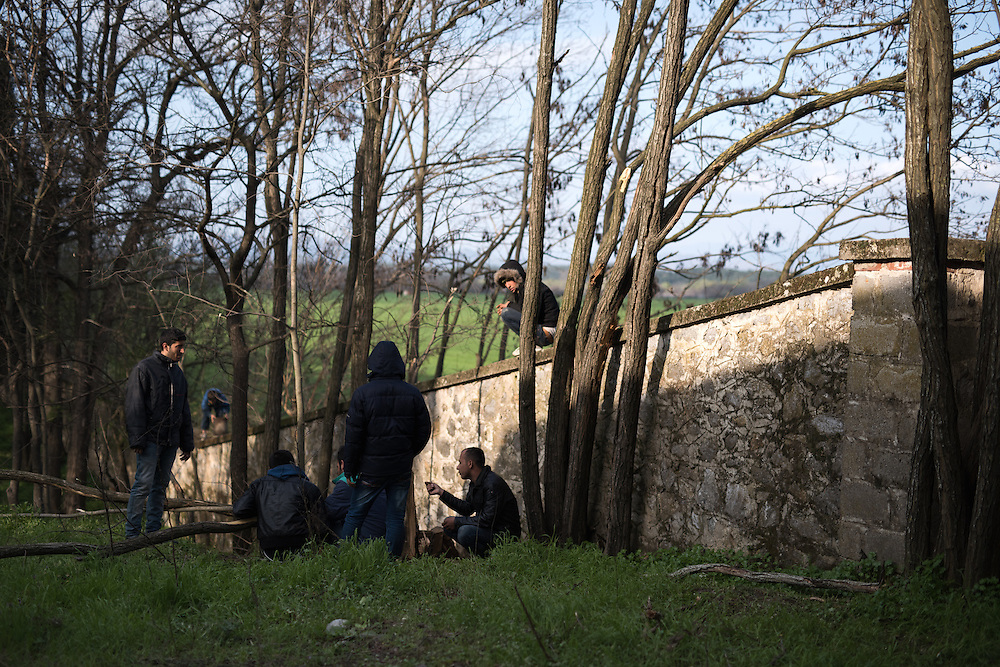 A group of Kurdish men chatting on the wall of the disused Centre of Sanitary Veterinary Control of Idomeni. <br /> <br /> Thousands of refugees are stranded in Idomeni unable to cross the border. The facilities are stretched to the limit and the conditions are appalling.