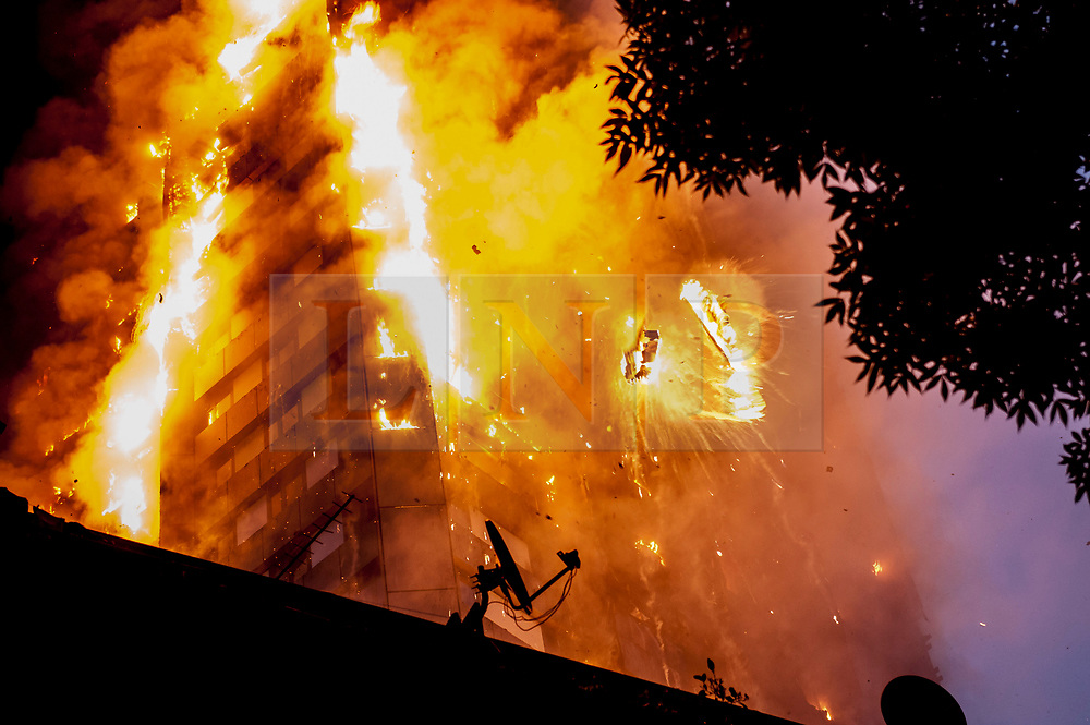 © Licensed to London News Pictures. 14/06/2017. London, UK. Falling burning debris at the scene of a huge fire at Grenfell tower block in White City, London. The blaze engulfed the 27-storey building with 200 firefighters attending the scene. There were reports of people trapped in the building. Photo credit: Guilhem Baker/LNP