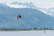 A kite surfer rides past snow capped mountains on 20 Mile River near Portage, Alaska.
