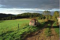 Path in Haute-Loire (Auvergne-France) at sunrise with an old car (a 203 Peugeot) by the side.<br /> <br /> Chemin en Haute-Loire (Auvergne) au levé du soleil avec une vieille voiture (une 203 break) sur le bas-côté.