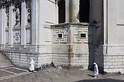 Two nuns walk in afternoon heat under the walls of Santa Maria della Salute church in Dorsoduro, a district of Venice, Italy.