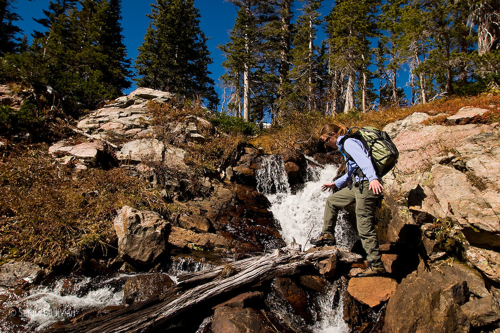 Amy Townsend crosses a creek via a log in the James Peak Wilderness in late Autumn in Colorado.