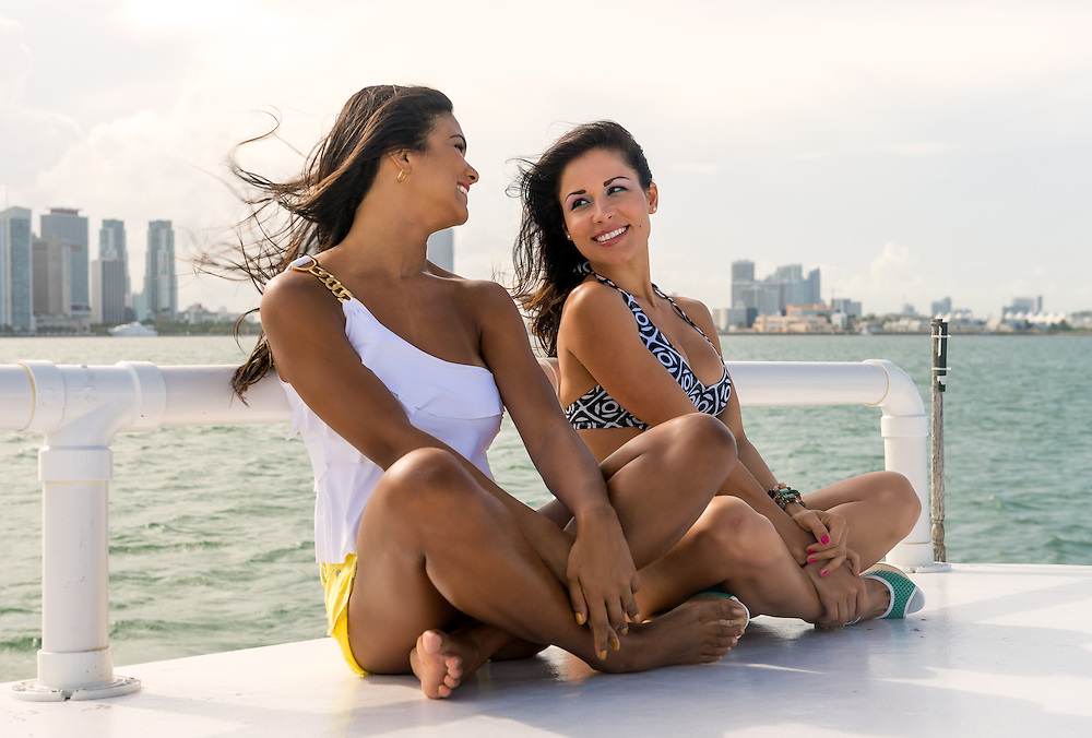 Two female friends sitting on the quay in a close up shot having fun with Miami skyline behind