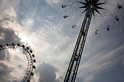 Rising circular fairground ride with EU member flags and Millennium (ferris) Wheel on London's Southbank.