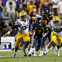 Sep 25, 2010; Baton Rouge, LA, USA; West Virginia Mountaineers running back Noel Devine (7) runs away from LSU Tigers defenders defensive tackle Lazarius Levingston (95) and defensive tackle Drake Nevis (92) during the second half at Tiger Stadium. LSU defeated West Virginia 20-14.  Mandatory Credit: Derick E. Hingle