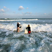Surfers make their way into the waves at Wrightsville Beach, NC...