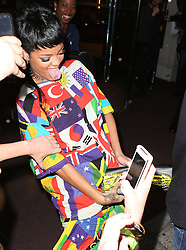 Singer Rihanna wearing a flag suit and carrying a Vivienne Westwood clutch bag with a gold penis on it, jokes around with the bag as she leaves her hotel in London, UK. 11/09/2013<br /> BYLINE MUST READ : JAMESY/GOTCHA IMAGES<br /> <br /> Copyright by &copy; Gotcha Images Ltd. All rights reserved.<br /> Usage of this image is conditional upon the acceptance <br /> of Gotcha Images Ltd, terms and conditions available at<br /> www.gotchaimages.com