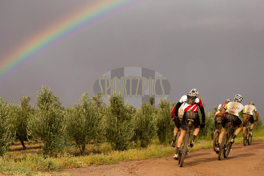 Riders leave water point 1 to follow the rainbow during stage 5 of the 2012 Absa Cape Epic Mountain Bike stage race from the Overberg Primary & High School in Caledon to Oak Valley Wine Estate in the Elgin Valley, South Africa on the 30 March 2012..Photo by Nick Muzik/Cape Epic/SPORTZPICS