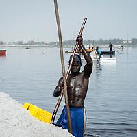 Un homme charge sa barque de sel.