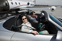 Mid-adult businesswoman and mid-adult businessman sitting in convertible on landing strip.