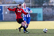 Hassocks' Joanne Brown releases the ball before being tackled by Jay Blackie during the FA Women's Sussex Challenge Cup semi-final match between Brighton Ladies and Hassocks Ladies FC at Culver Road, Lancing, United Kingdom on 15 February 2015. Photo by Geoff Penn.