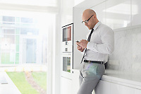 Side view of mid adult businessman using cell phone at home