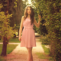 Young girl with pale skin and long blond hair in a pale pink dress standing in a garden