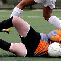 Scotts Valley High keeper Emily Johnson gets a cleat to her neck from Santa Cruz High forward Kiara Burkett as she makes a save for the Falcons during the team's 1-0 loss to Santa Cruz on February 7.<br />Photo by Shmuel Thaler/Santa Cruz Sentinel