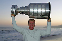 24 August 2002: Detroit Red Wings professional hockey player and goaltender Kris Draper, 31 lifts the NHL Stanley Cup over his head at sunset on the beach at the Pacific Ocean. .