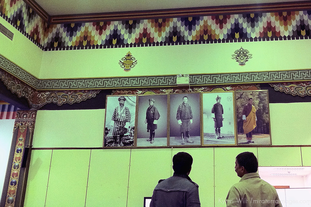 Asia, Bhutan, Paro. Two Bhutanese men pay respect to portraits of the Five Kings of Bhutan in the airport at Paro.