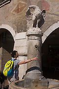 Frescoes and tourist taking fresh drinking water fountain in Piazza Duomo, Trento.