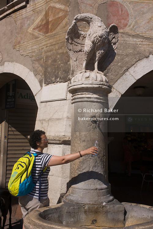Frescoes and tourist taking fresh drinking water fountain in Piazza Duomo, Trento.