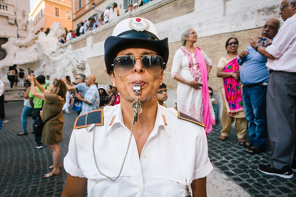 ROME, ITALY - 20 JUNE 2017: A Roman policewoman, entrusted to protect the Fountain of Trevi, blows his whistle at tourists that are eating ice cream by the fountain in Rome, Italy, on June 20th 2017.<br /> <br /> The warm weather has brought a menacing whiff of tourists behaving badly in Rome. On April 12, a man went skinny-dipping in the Trevi fountain resulting in a viral web video and a 500 euro fine.<br /> <br /> Virginia Raggi, the mayor of Rome and a national figurehead of the anti-establishment Five Star Movement,  issued an ordinance involving harsher fines for eating, drinking or sitting on the fountains, for washing animals or clothes in the fountain water or for throwing anything other than coins into the water of the Trevi Fountain, Bernini&rsquo;s Four Fountains and 35 other city fountains of artistic or historic significance around the city.  &ldquo;It is unacceptable that someone use them to go swimming or clean themselves, it&rsquo;s an historic patrimony that we must safeguard,&rdquo; Ms. Raggi said.