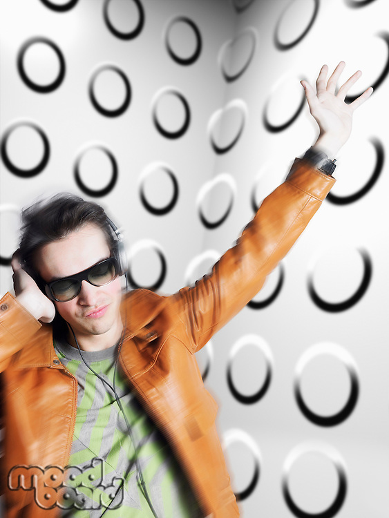 Man wearing headphones and sunglasses blurred motion in front of spotty wall