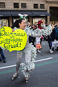 """New York, NY, USA-27 March 2016. Marni Halasa, a familiar fixture at New York City parades and other events, on roller skates and with a sign reading """"Bunnies vs. Corporarte Greed."""""""
