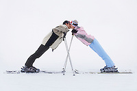 Couple leaning towards each other standing on skis side view
