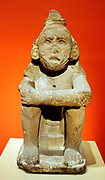 Aztec Standard Bearer. Seated on a small plinth with arms on knees and legs drawn up towards the body, this male figure wears an important headdress that was once topped with five tall tufts.  The tufts, related to the crest of a great curassow, are now missing, but in the back, the head covering still hangs onto the shoulders, wherre the figure's name 5 Serpent, is carved.