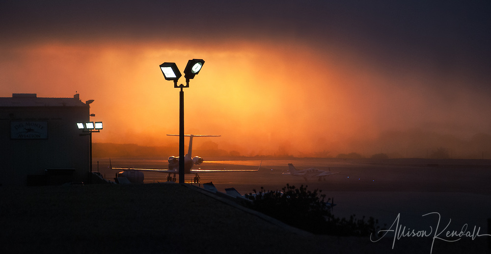 A vivid sunset and heavy fog set the mood at Monterey Airport