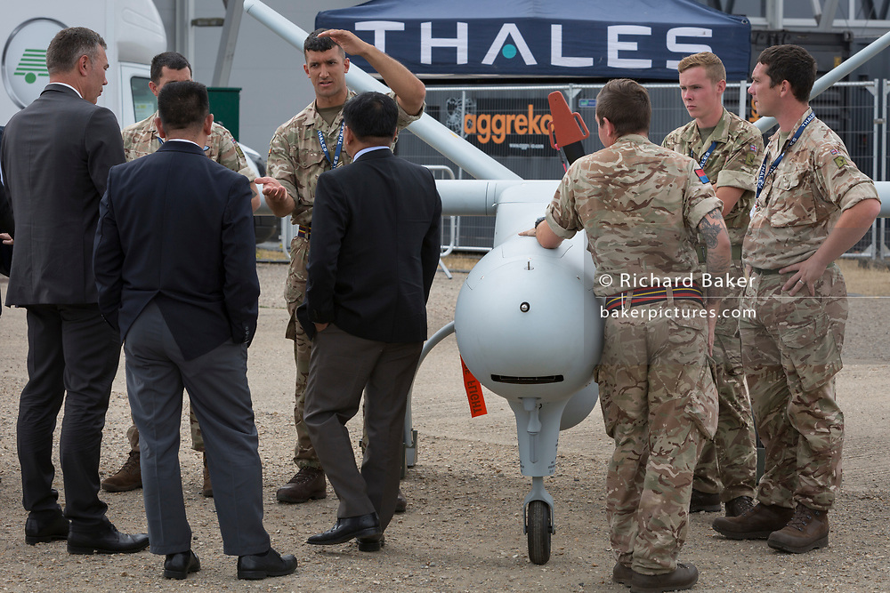 A foreign delegation listens to a briefing by a member of the British Army's Royal Artillery, demonstrating a Thales Watchkeeper UAV at the Farnborough Airshow, on 18th July 2018, in Farnborough, England.