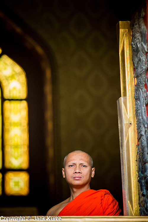 "25 FEBRUARY 2013 - BANGKOK, THAILAND: A Buddhist monk looks out a window at Wat Benchamabophit Dusitvanaram (popularly known as either Wat Bencha or the Marble Temple) on Makha Bucha Day. Makha Bucha is a Buddhist holiday celebrated in Myanmar (Burma), Thailand, Cambodia and Laos on the full moon day of the third lunar month (February 25 in 2013). The third lunar month is known in Thai is Makha. Bucha is a Thai word meaning ""to venerate"" or ""to honor"". Makha Bucha Day is for the veneration of Buddha and his teachings on the full moon day of the third lunar month. Makha Bucha Day marks the day that 1,250 Arahata spontaneously came to see the Buddha. The Buddha in turn laid down the principles his teachings. In Thailand, this teaching has been dubbed the 'Heart of Buddhism'.      PHOTO BY JACK KURTZ"
