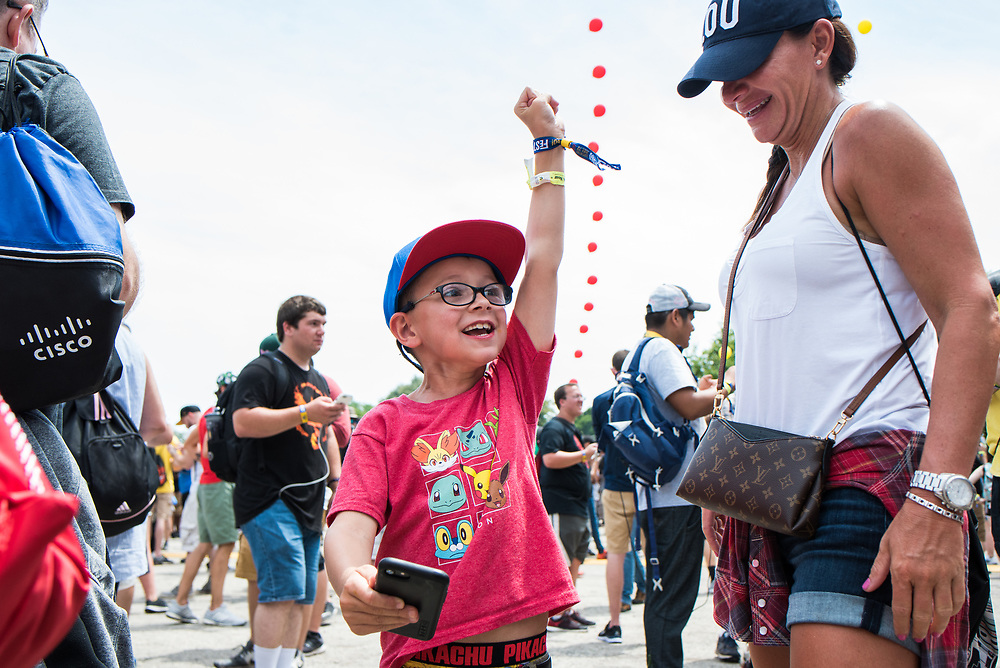 "Tyler Vaughan celebrates after catching a ""mystical Unown"" alongside his mother, Helen Vaughan, at Pokémon GO Fest in Grant Park on July 22, 2017."