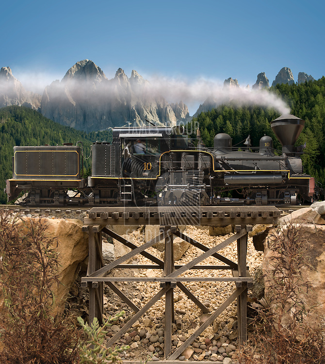 Steam locomotive going over a wooden trestle bridge with mountains in the background