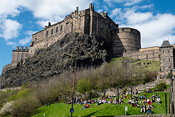 View of Edinburgh Castle from Grassmarket on sunny day with people sitting on grass, Old Town, Edinburgh, Scotland, UK