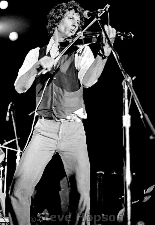 """John Hartford at the Armadillo World Headquarters in Austin Texas March 23, 1979.  Hartford (December 30, 1937? June 4, 2001) was an American folk, country and bluegrass composer and musician known for his mastery of the fiddle and banjo, as well as for his witty lyrics, unique vocal style, and extensive knowledge of Mississippi River lore. Hartford recorded several songs for the soundtrack to the movie O Brother, Where Art Thou, and won a Grammy for his performance. Hartford wrote the Glen Campbell hit, """"Gentle On My Mind,"""" which is one of the most widely recorded country songs. Hartford performed with a variety of ensembles throughout his career, and is perhaps best known for his solo performances where he would interchange the guitar, banjo, and fiddle from song to song. He also invented his own shuffle tap dance move, and clogged on an amplified piece of plywood while he played and sang.  Hartford died of non-Hodgkin's Lymphoma, on June 4, 2001 in Nashville Tennessee...The Armadillo World Headquarters was a legendary club in Austin Texas that was torn down in 1981."""