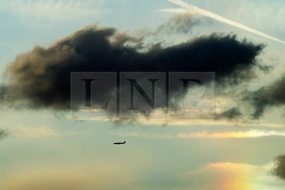 © Licensed to London News Pictures. 26/04/2019.<br /> Orpington,UK. A plane flying under Dark rain clouds over South East London this evening as the sun sets. Storm Hannah weather warning has been issued with strong winds up to 80mph expected. Photo credit: Grant Falvey/LNP