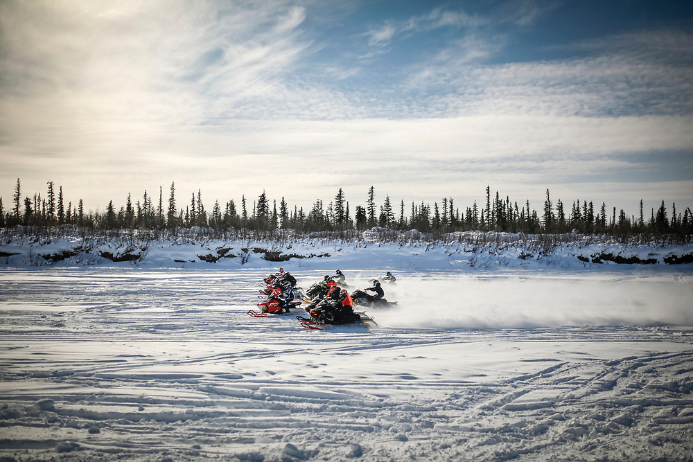 Snowmobiles jump off the starting line during the Inuvik Muskrat Jamboree snowmobile races.