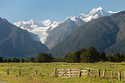 A rustic fence with Fox Glacier and Mount Cook off in the distance