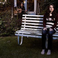A young woman sitting on a white garden seat while a young man plays guitar