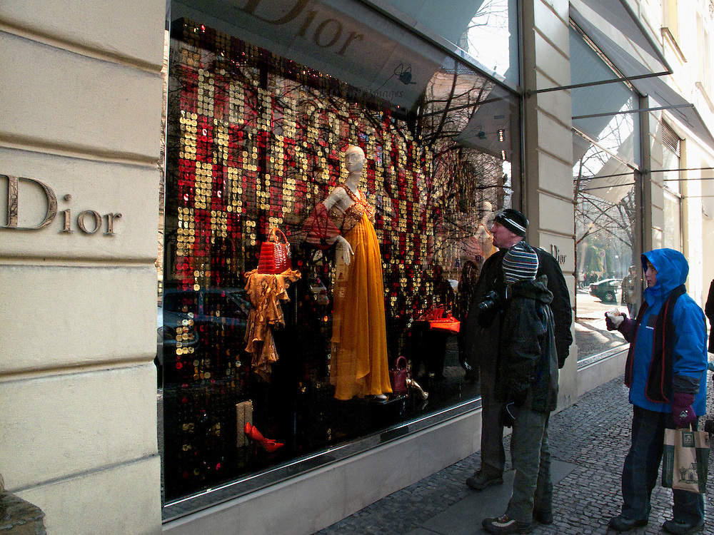 Pedestrians, one man and two women, pause to look in the window of the Dior boutique in Old Prague.  Mannequin in the window wears an orange colored gown.  Accessories nearby in red and orange glow richly.