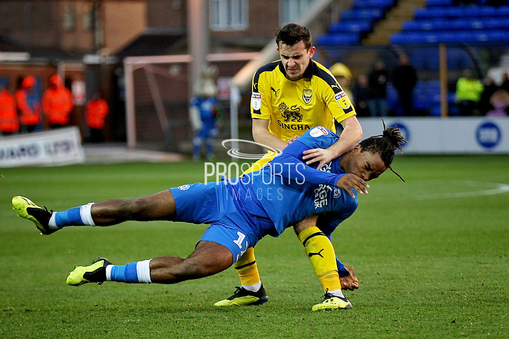 Oxford United's Jamie Hanson (6) fouls Peterborough United forward Ivan Toney (17) during the EFL Sky Bet League 1 match between Peterborough United and Oxford United at London Road, Peterborough, England on 8 December 2018.