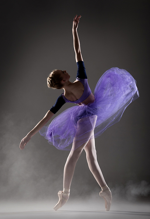 Classical ballet dancer, Maeve Maguire, in a purple romantic tutu, in the studio on a black background. Photograph taken in San Francisco by Rachel Neville.