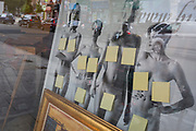 The private parts of naked women models, photographed in black and white by German-Australian photographer Helmut Newton, have been censored with post-it notes in the window of a picture framers in Bermondsey, on 15th August 2019, in London, England.