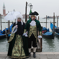 VENICE, ITALY - FEBRUARY 11:  A  couple wearing Carnival costumes poses for pictures in front of the gondolas in St Mark's Square on February 11, 2012 in Venice, Italy.The annual festival, which lasts nearly three weeks, will see the streets and canals of Venice filled with people wearing highly-decorative and imaginative carnival costumes and masks.