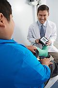 Doctor preparing to check boy's blood pressure