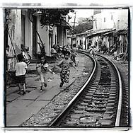 Vietnamese kids running along the railway of Hanoi, Vietnam, Southeast Asia
