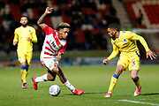 Mallik Wilks of Doncaster Rovers takes on Tareiq Holmes-Dennis of Bristol Rovers during the EFL Sky Bet League 1 match between Doncaster Rovers and Bristol Rovers at the Keepmoat Stadium, Doncaster, England on 26 March 2019.