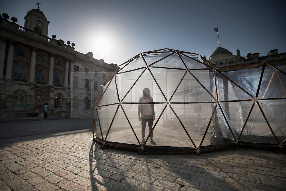 © Licensed to London News Pictures. 18/04/2018. London, UK. A visitor walks through one of British artist Michael Pinsky's Pollution Pods, a new sensory work installed at Somerset House in London to mark Earth Day 2018. A series of five connecting domes recreate the pollution from London, Beijing, São Paulo, New Delhi and Tautra in Norway. Visitors are invited to experience first-hand the difference in the air quality of global environments. The Pollution Pods are open until 25th April 2018, including Earth Day on the 22nd April. Photo credit: Peter Macdiarmid/LNP