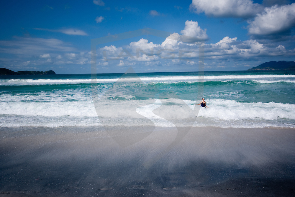 woman swimming in the rough ocean tide of the atlantic ocean at the white sands of cabo frio beach in rio de janeiro, brazil