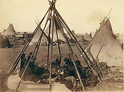 Oglala women and children seated inside an uncovered tepee frame in an encampment - most are looking away from the camera - probably on or near Pine Ridge Reservation. 1891. Photograph by John C. H.Grabill (active  1887-1891).